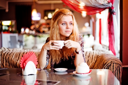 A young woman having lunch at a cafe laughing photo
