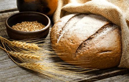 comiendo pan: pan fresco y trigo en la madera Foto de archivo