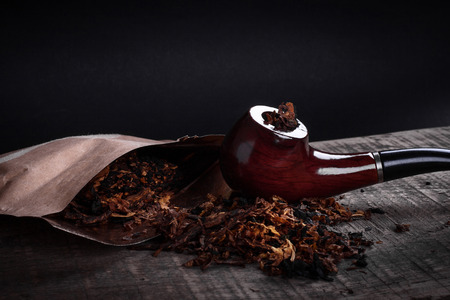 pipe and tobacco on a wooden surface photo
