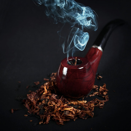 pipe and tobacco on a wooden surface, soft focus