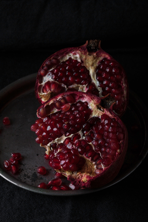 Beautiful juicy red garnet on a dark background. Diet can be beautiful 스톡 콘텐츠