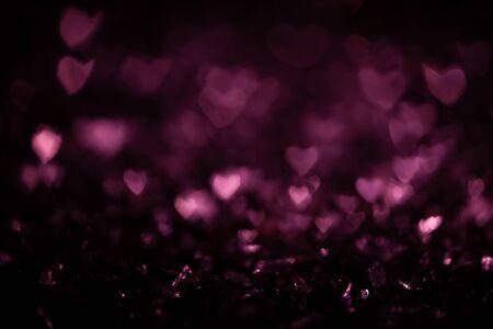 Dark abstract background with pink bokeh defocused lights heart shape 写真素材