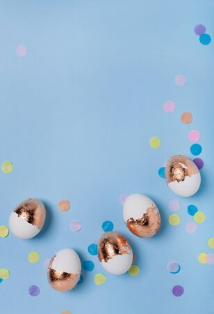 Cute light blue background with gilded eggs and confetti.