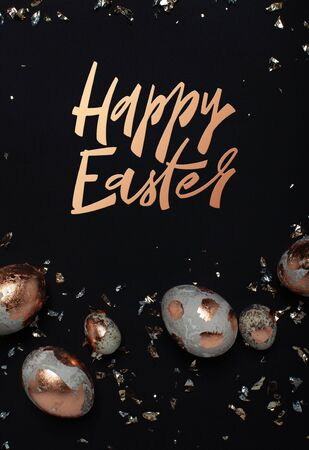 Happy Easter minimalistic concept with hand drawn modern lettering. Gilded eggs and shiny confetti on a black background.
