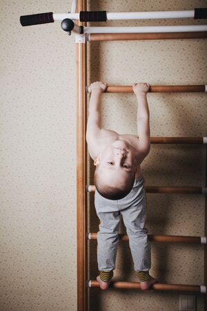 Home workout. The boy hangs head down on the horizontal bar.