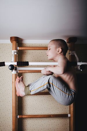 Home workout. The boy raises his legs in the hang. Фото со стока
