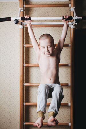 Home workout. The boy raises his legs in the hang. Imagens