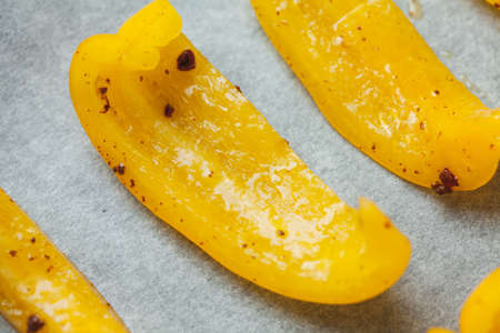 Slices of yellow bell pepper prepared for baking with spices, close up