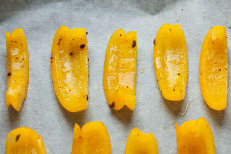 Bright slices of bell pepper prepared for baking in the oven. Soft focus. Foto de archivo