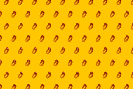 Vitamin D concept in the sunlight. Vitamin gelatin capsules laid out in even rows on yellow background