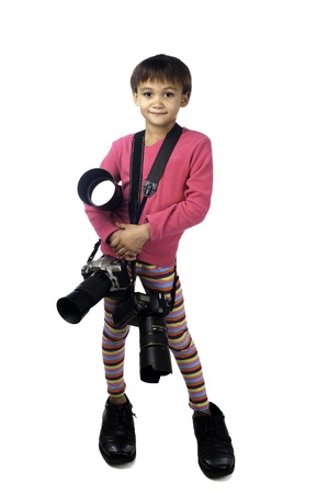 A young girl tries to emulate her photographer father by wearing his shoes and carrying his equipment.