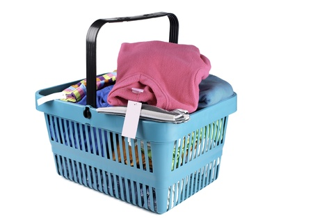 A shopping basket filled with tagged clothes, sits on a white background. Stock Photo