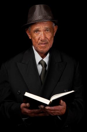 predicador: Un anciano tiene un libro sagrado en sus manos en su búsqueda de respuestas.