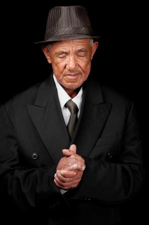 faithful: A senior man folds his hands whilst praying.