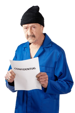 An older male cries when reading a confidential note.