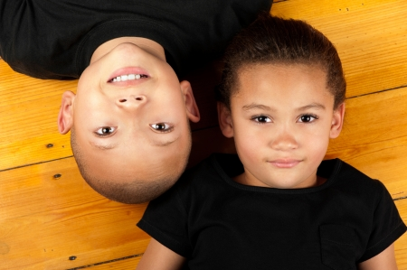 A brother and his sister relax whilst lying on wooden floor.