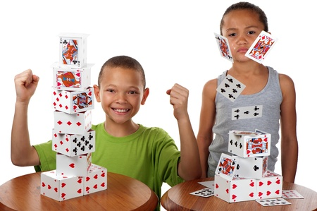 A young boy smiles happily when he wins a card building competition against his siter, whose tower collapses.