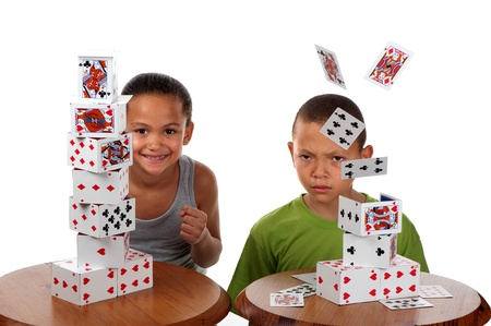 A young girl smiles happily when she wins a card building competition against her brother, whose tower collapses. Stock Photo