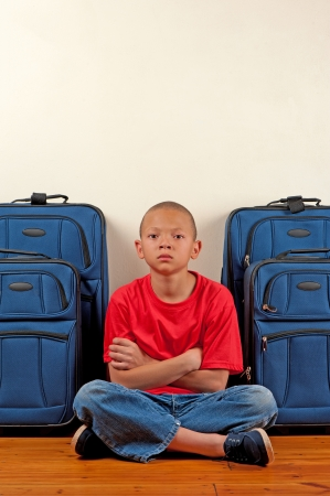 A boy sitting in front of suitcases appears upset.
