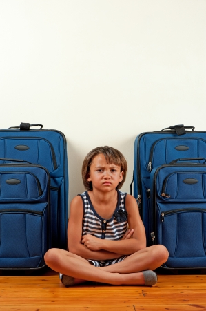 A young girl sits in front of suitcases, with a sad expression on her face. Stock Photo - 16878692