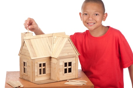 A smiling young boy stands next to the ice-cream house he is building