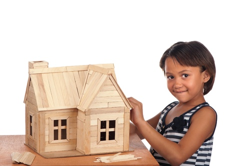 A smiling young girl stands next to the ice cream house she is building  Stock Photo