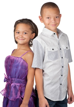 A brother and sister smile happily whilst standing close to each other  photo