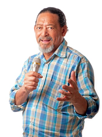 A senior male expresses musical notes whilst holding a microphone in his hand