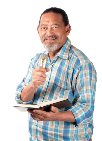 A senior preacher with a microphone and book appears as happy as can be  Stock Photo
