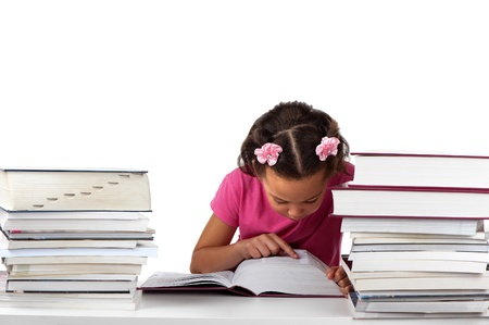 reading material: A young girl stays focused whilst reading a huge book in the midst of other reading material