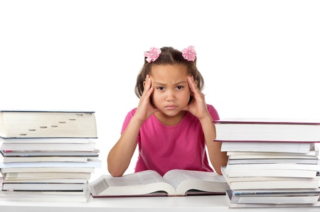 A young girl holds her head in a frown at a desk covered with many big books.