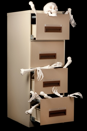 Skeletons in a cabinet are partially revealed in this low key image. Stock Photo