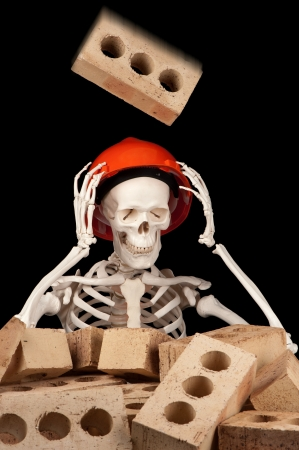 A falling brick is about to make contact with a hard hat on the skull of a skeleton