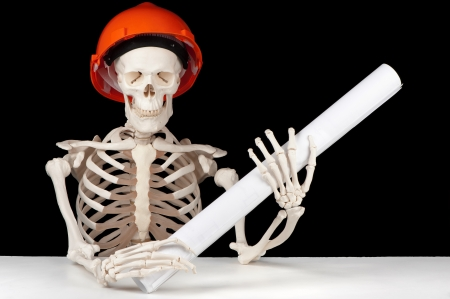A skeletal architect with hard hat and building plan symbolizes planning that happened too late  Stock Photo