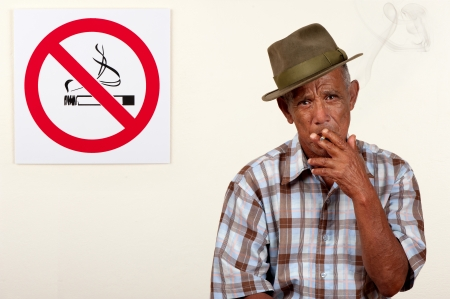 disobey: A senior citizen pays scant regard to a non-smoking sign.