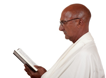 Side profile of a senior man concentrating heavily on a holy book he is reading. photo