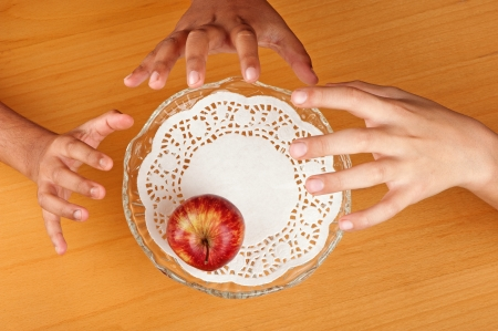 Children hands compete to grab the last apple available in a bowl. Stock Photo