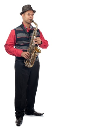 A young man plays his saxophone whilst standing upright