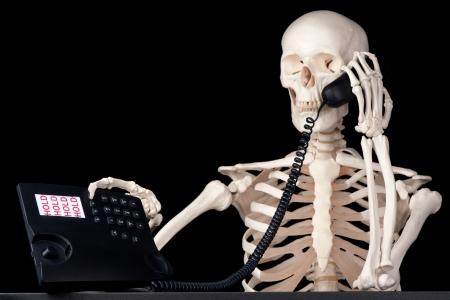 Een skelet call center medewerker houdt een gesprek in de wacht voor altijd Stockfoto