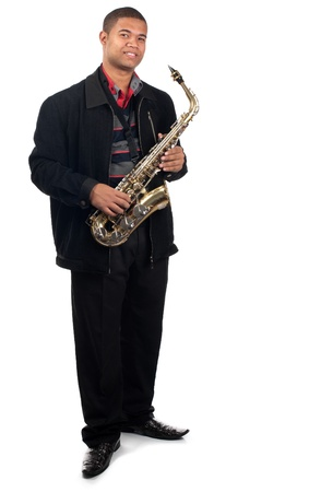 A proud young saxophonist holds his instrument.