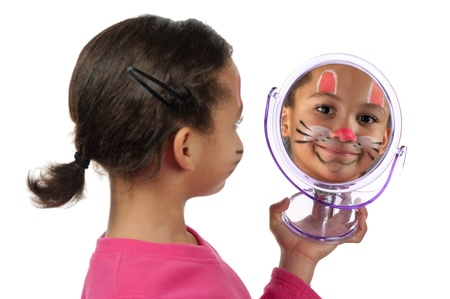 A young girl looks at herself in the mirror after her facial painting.