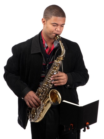 A young saxophonist plays by reading from a book on a stand.