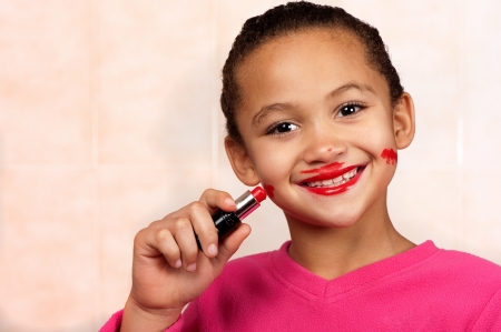 A smiling young girl applies lipstick in an unconventional manner.