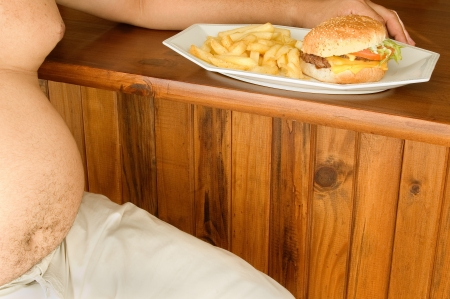A middle aged man sits next to a burger and fries ready to be eaten