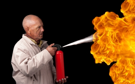 An old man attempts to extinguish the flames of a giant fire with a small extinguisher