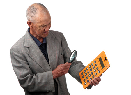 A senior person uses a magnifying glass to assist him to view a calculator. Stock Photo