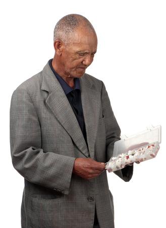autocuidado: Un hombre de edad estresado evalúa un recipiente lleno de una multitud de diferentes tabletas. Foto de archivo