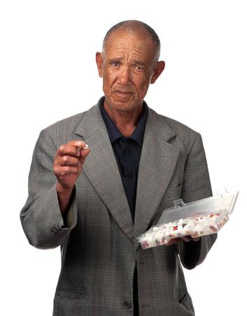autocuidado: Un jubilado se enfrenta con todas las tabletas que tiene que tomar en este momento de su vida. Foto de archivo