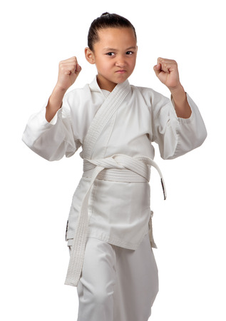 A young girl with white karate belt is ready to start her training.