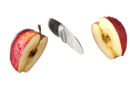 A knife and an apple cut in halves are frozen in mid air